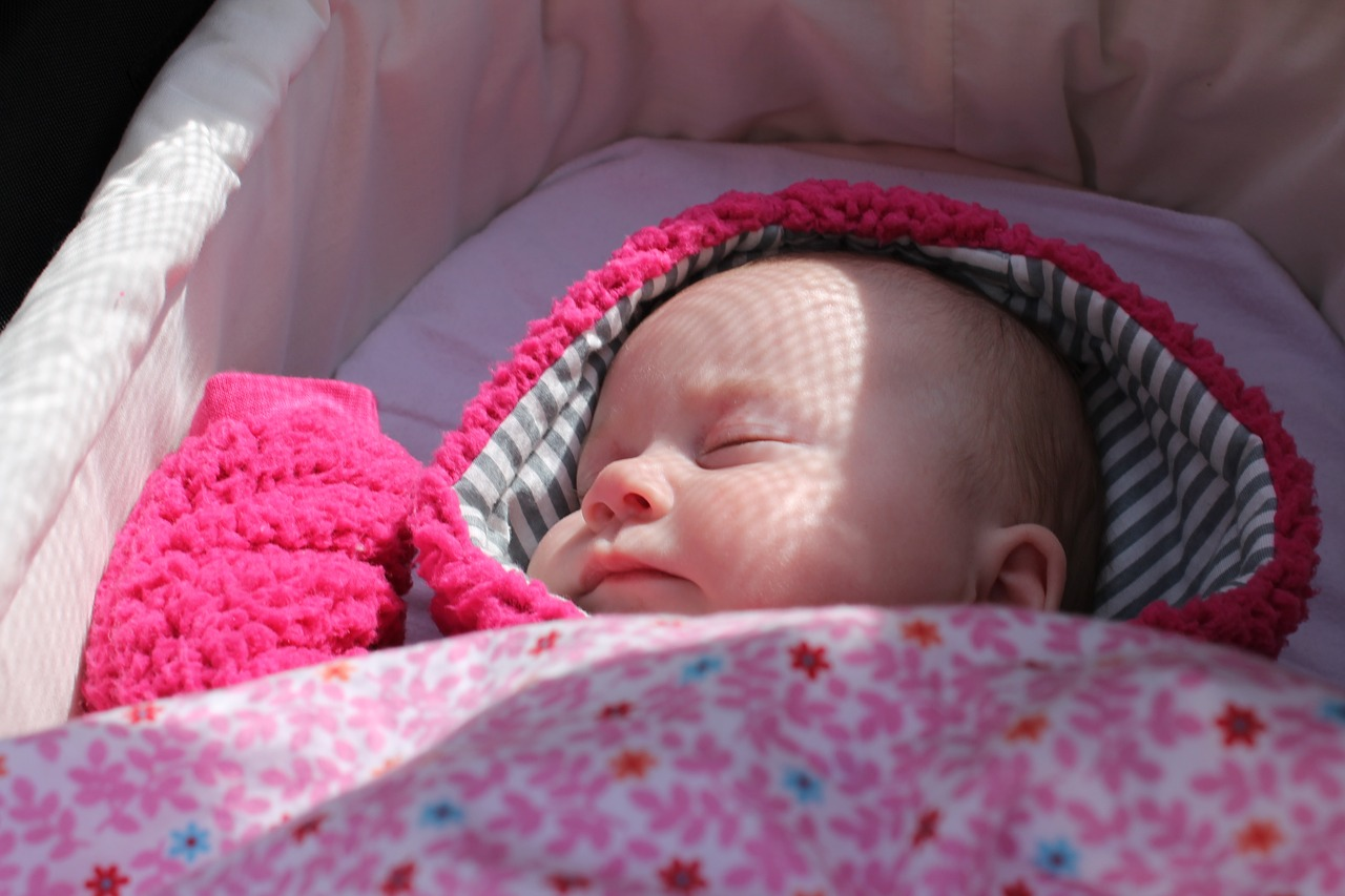 baby sleeping in the stroller with sunlight on her face