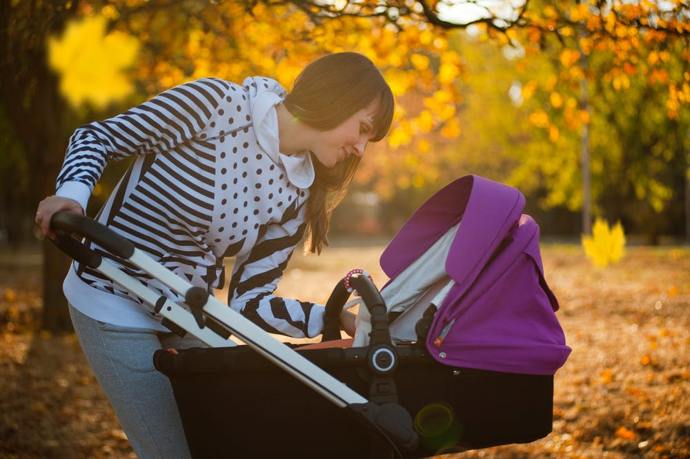 woman looking at her baby in the stroller